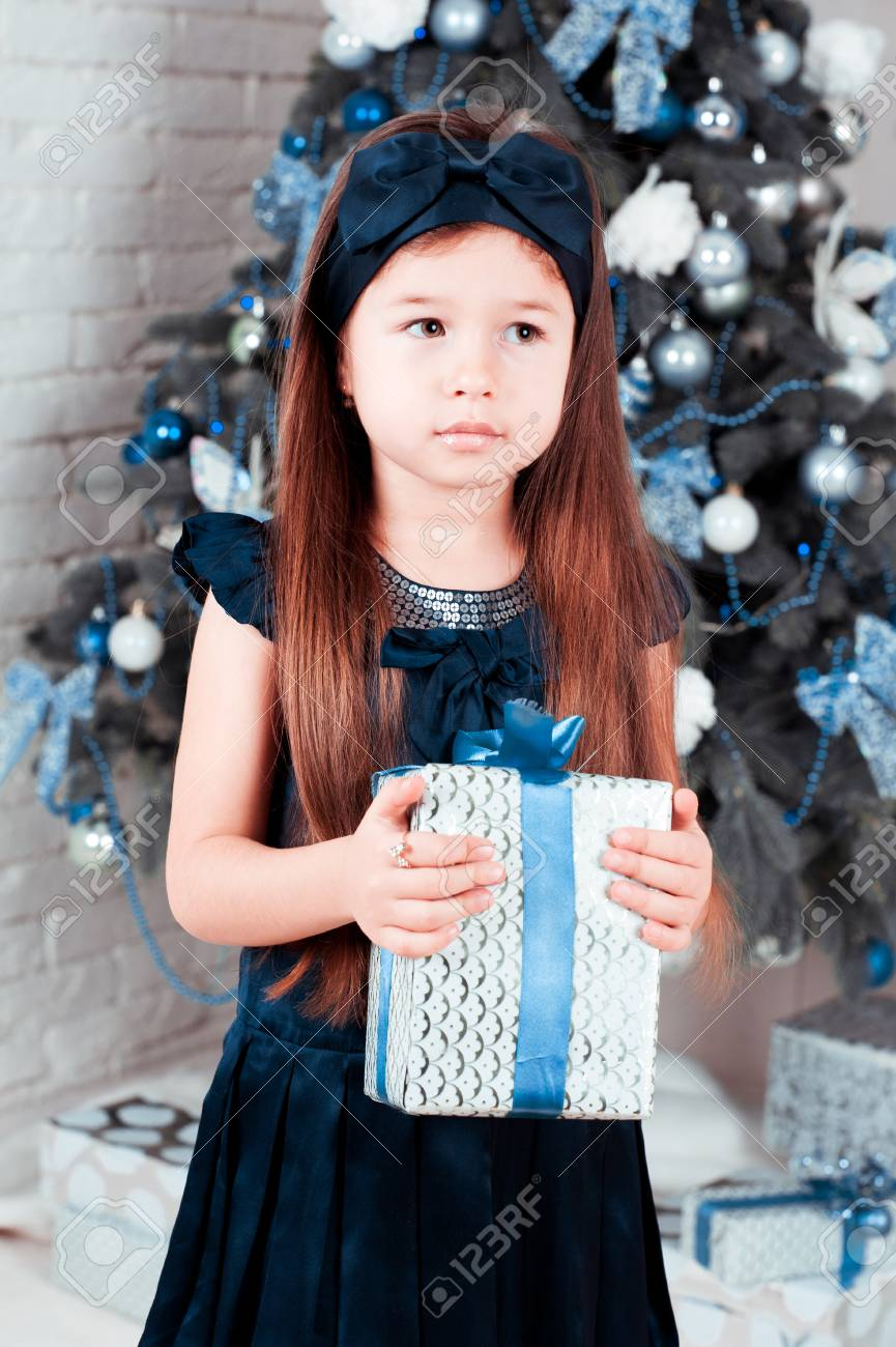 Cute Baby Girl 5-6 Year Old Holding Christmas Gift In Room ...