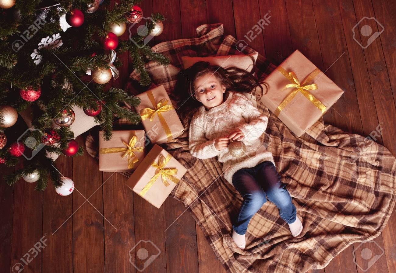 Kid Mädchen 4-5 Jahre Alt Liegend Unter Weihnachtsbaum Auf Holzboden ...