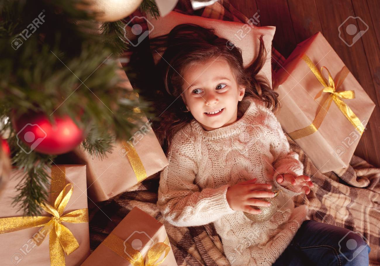 Cute girl 4-5 year old lying under christmas tree with many presents in room Girl Year Old Lying Under Christmas Tree With Many Presents