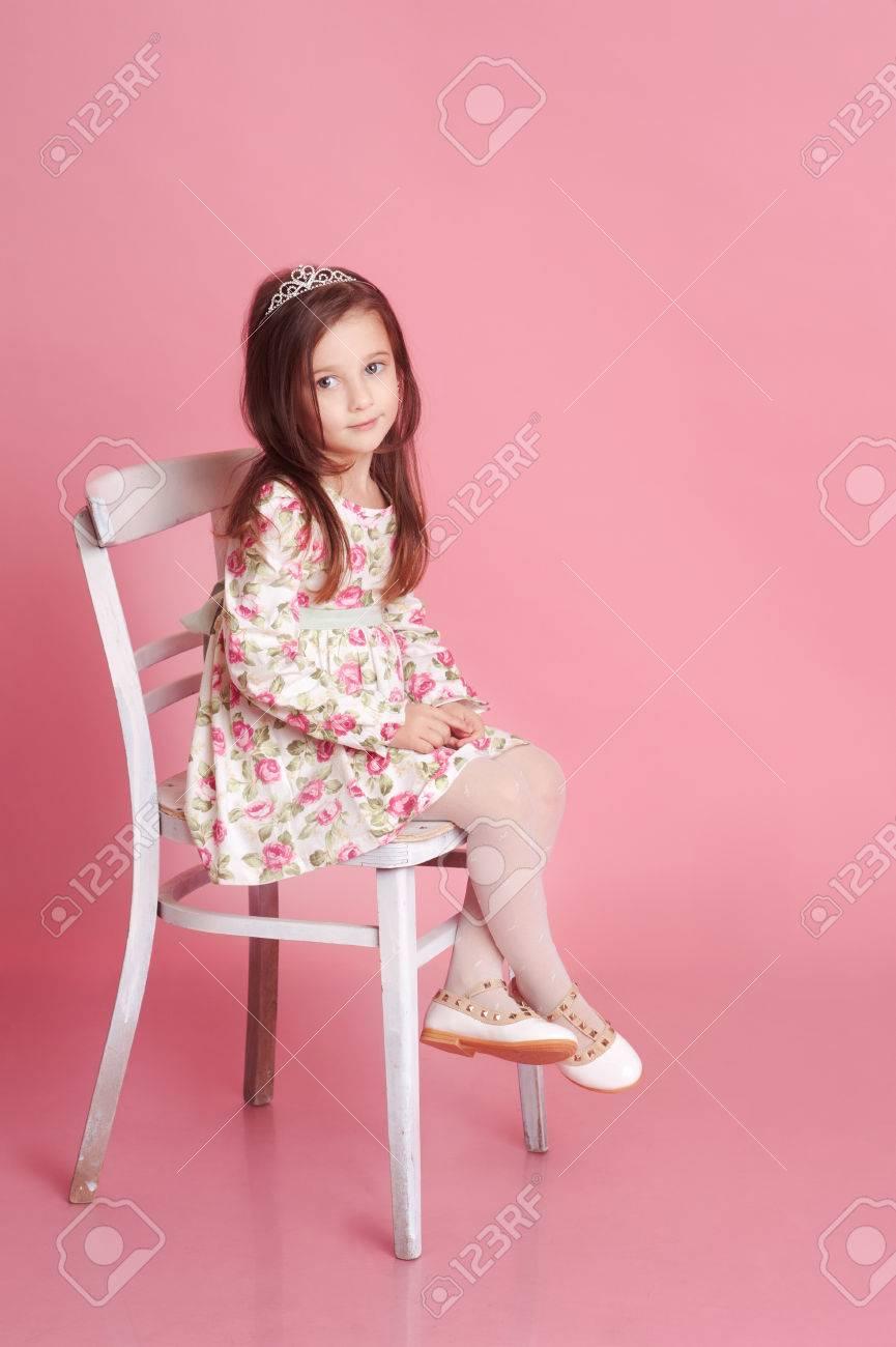 Bebé Lindo 4-5 Años Sentado En La Silla Blanca Sobre Rosa En La ...