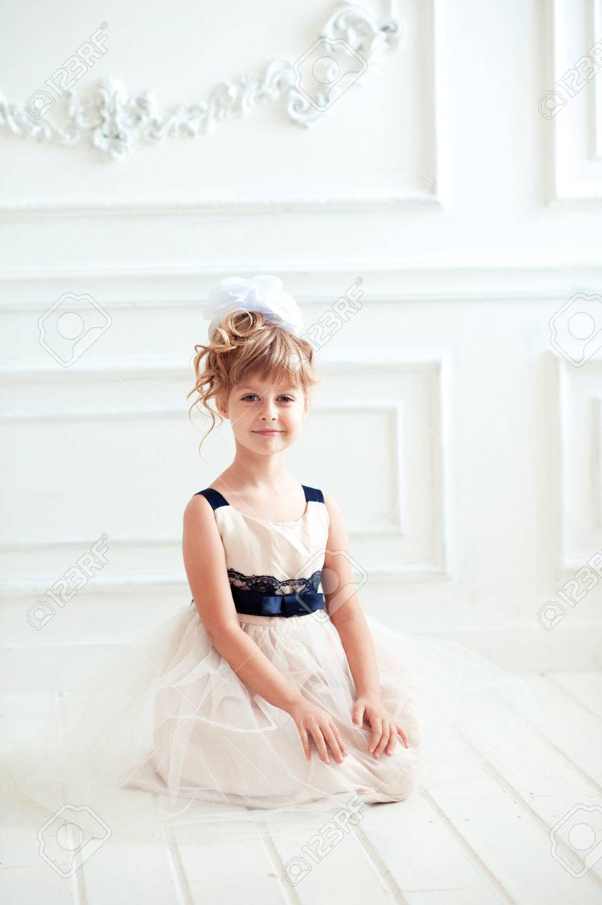Smiling Kid Girl 4 5 Year Old Wearing Birthday Style Dress In Room Sitting