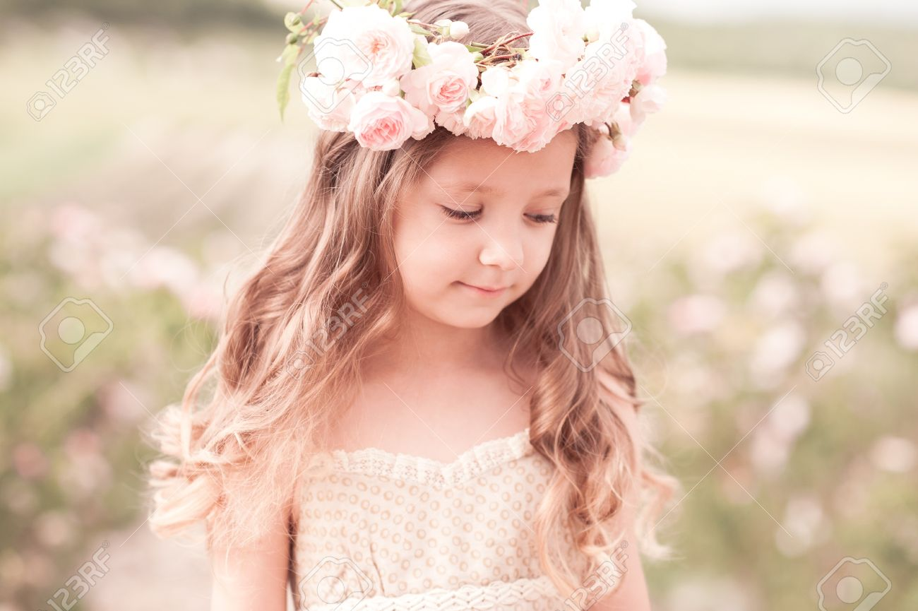 88d4801df0a7 Beautiful baby girl 4-5 year old wearing wreath with flowers outdoors.  Stylish child