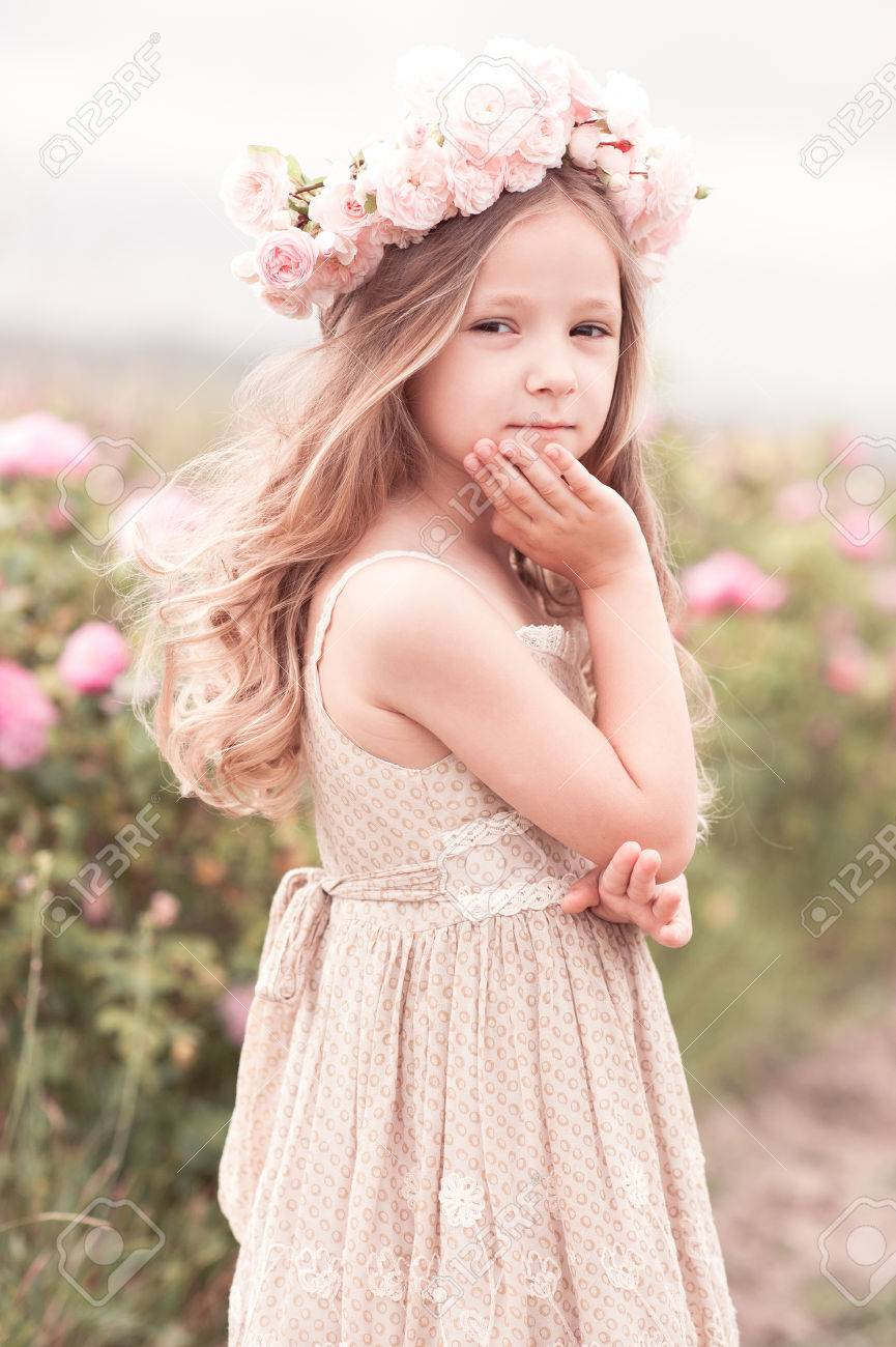 257d6e113743d Smiling baby girl 3-4 year old wearing stylish dress and wreath with roses  outdoors