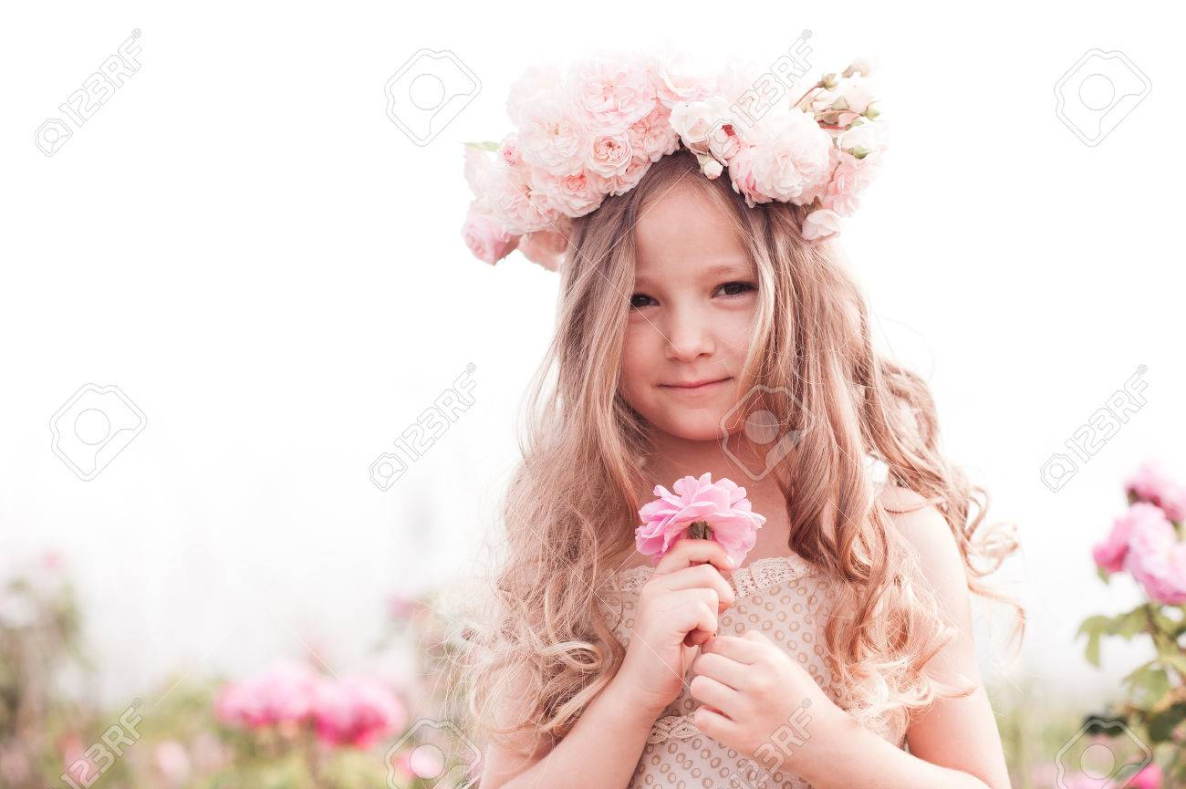 cute baby girl 3-4 year old holding flower rose outdoors. child