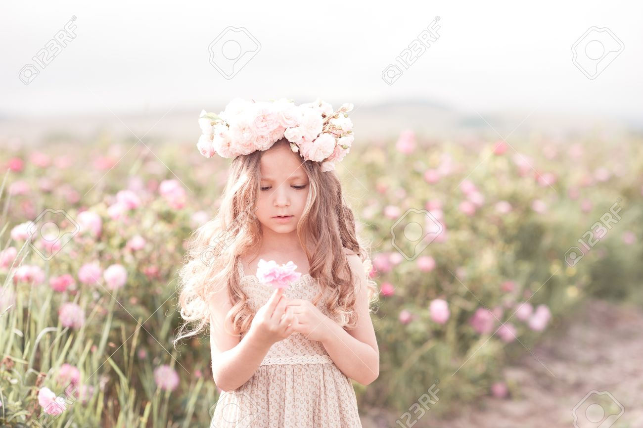 cute baby girl 4-5 year old holding rose flower in meadow. wearing