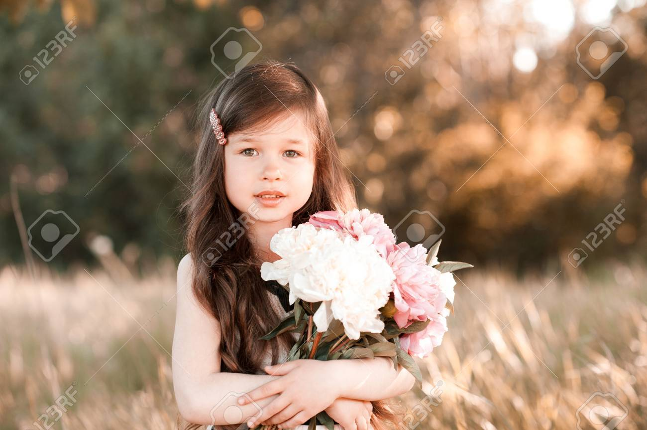 cute baby girl 4-5 year old holding flowers in field. looking