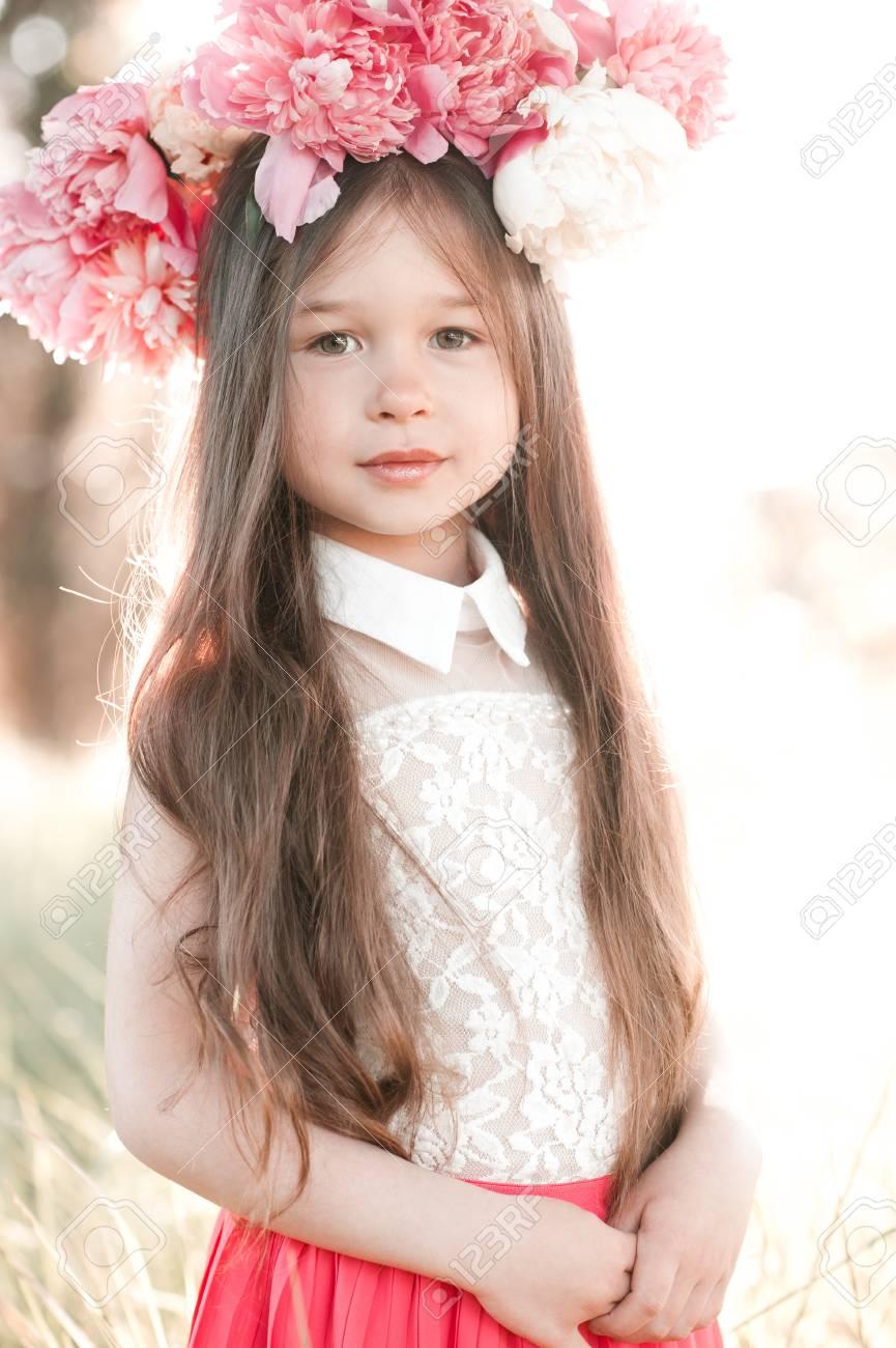 Schöne Kind Mädchen 11-11 Jahre alt trägt floral Frisur im Freien. Betrachtet  man die Kamera.
