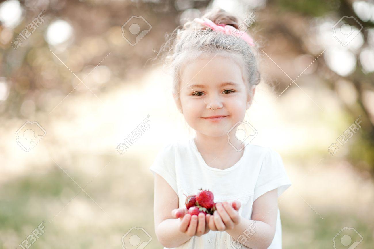cute kid girl 4-5 year old eating strawberries outdoors. looking