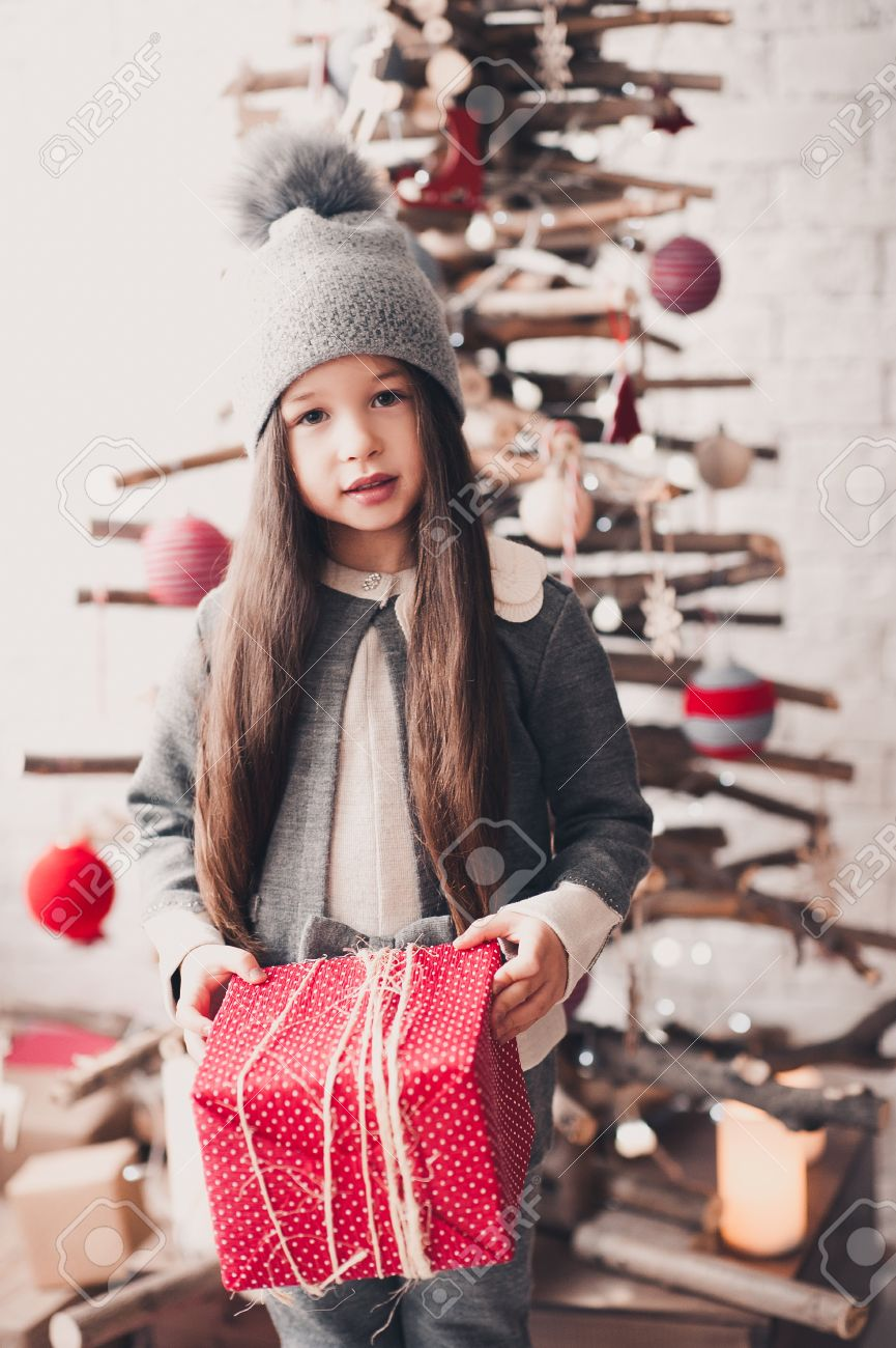Cute baby girl 4-5 year old wearing knitted clothes holding christmas present in room Baby Girl Year Old Wearing Knitted Clothes Holding