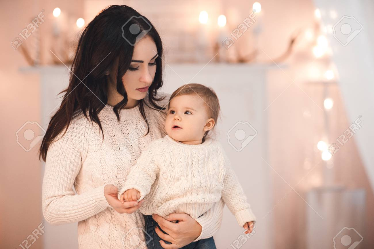Beautiful woman holding baby girl under 1 year old wearing knitted..