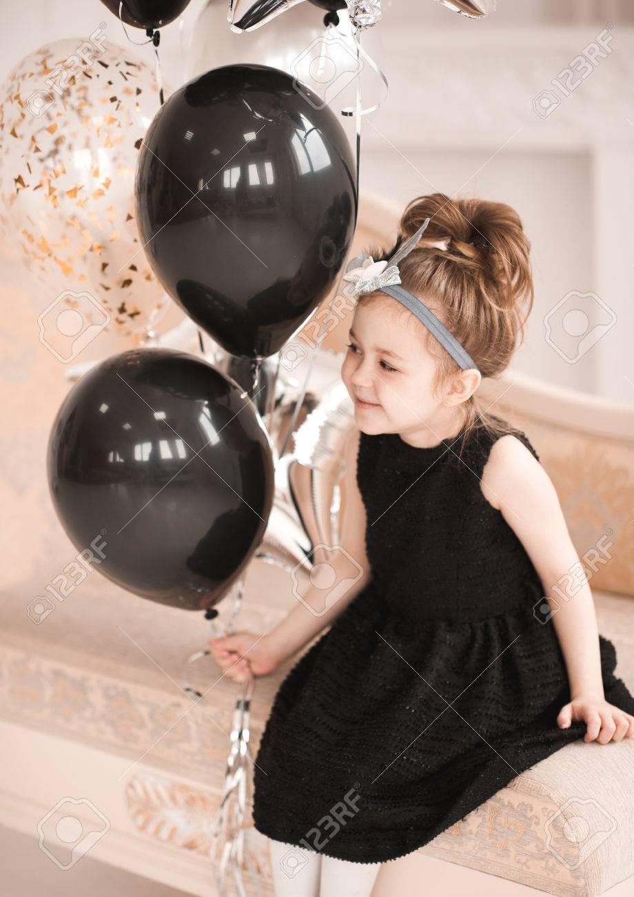 34cc41b89b0c Smiling Child Girl 5-6 Year Old Holding Black Balloons Sitting ...