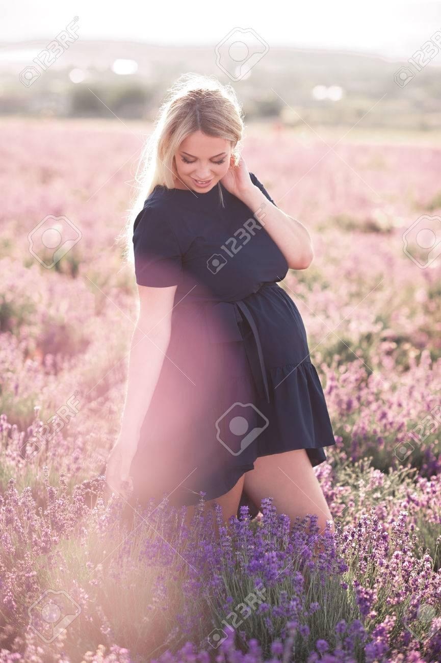 Beautiful blonde pregnant woman walking in lavender field wearing motherhood maternity beautiful blonde pregnant woman walking in lavender field wearing stylish blue dress outdoors summer ombrellifo Choice Image