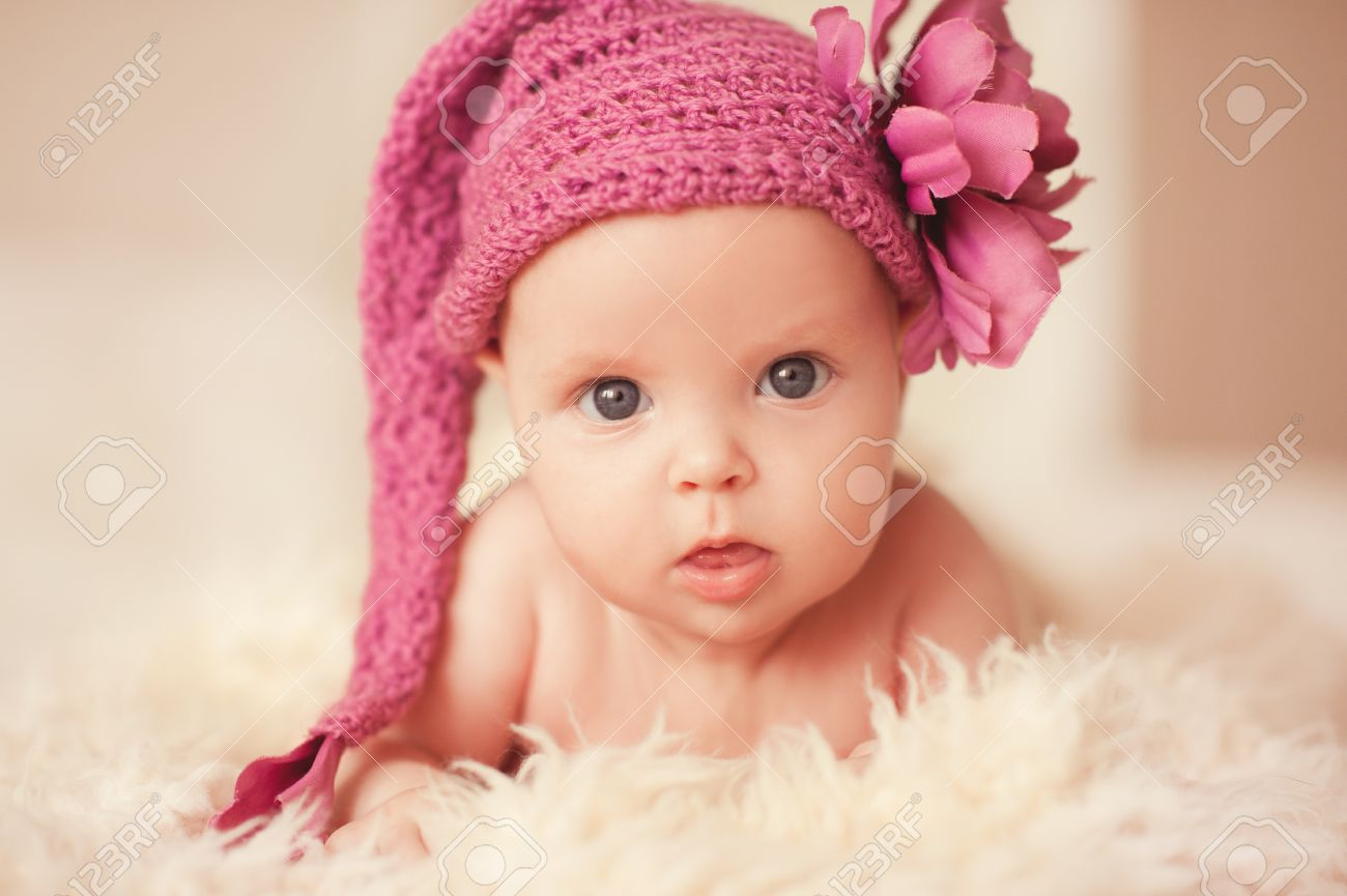 cute baby girl 2-3 month old wearing knitted pink hat with