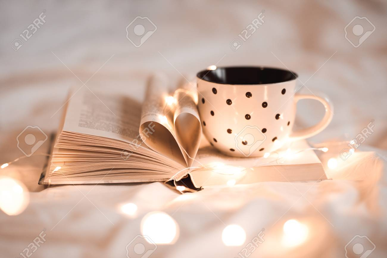 Open book with folded sheets in heart shape and cup of tea in bed with Christmas lights closeup. Good morning. Breakfast time. - 90599980