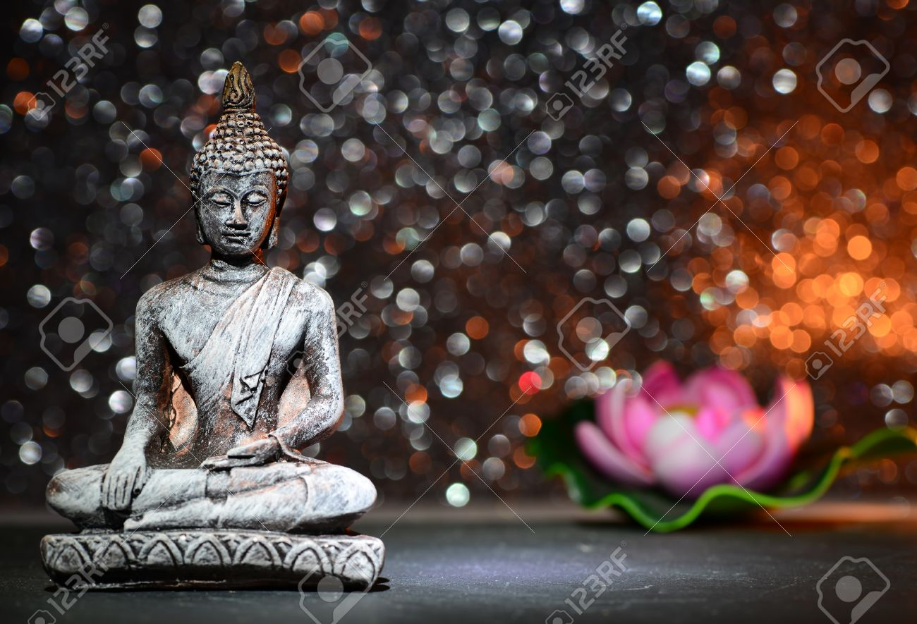 Zen Buddha Statue And A Lotus Flower On A Bright Shiny Glitter