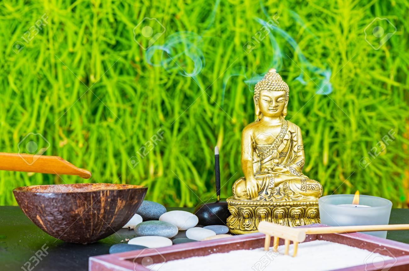 bouddha, bâton d'encens, bougie, râteau, sable et pierres zen comme