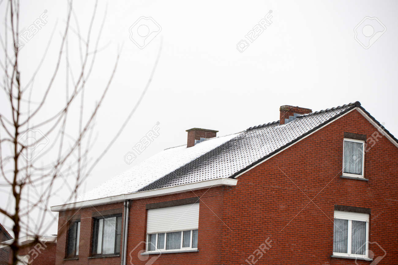 A portrait of two semi-detached buildings with white snow on their roofs during winter. The snow on one of the houses is already melting due to a badly isolated roof. - 165461935