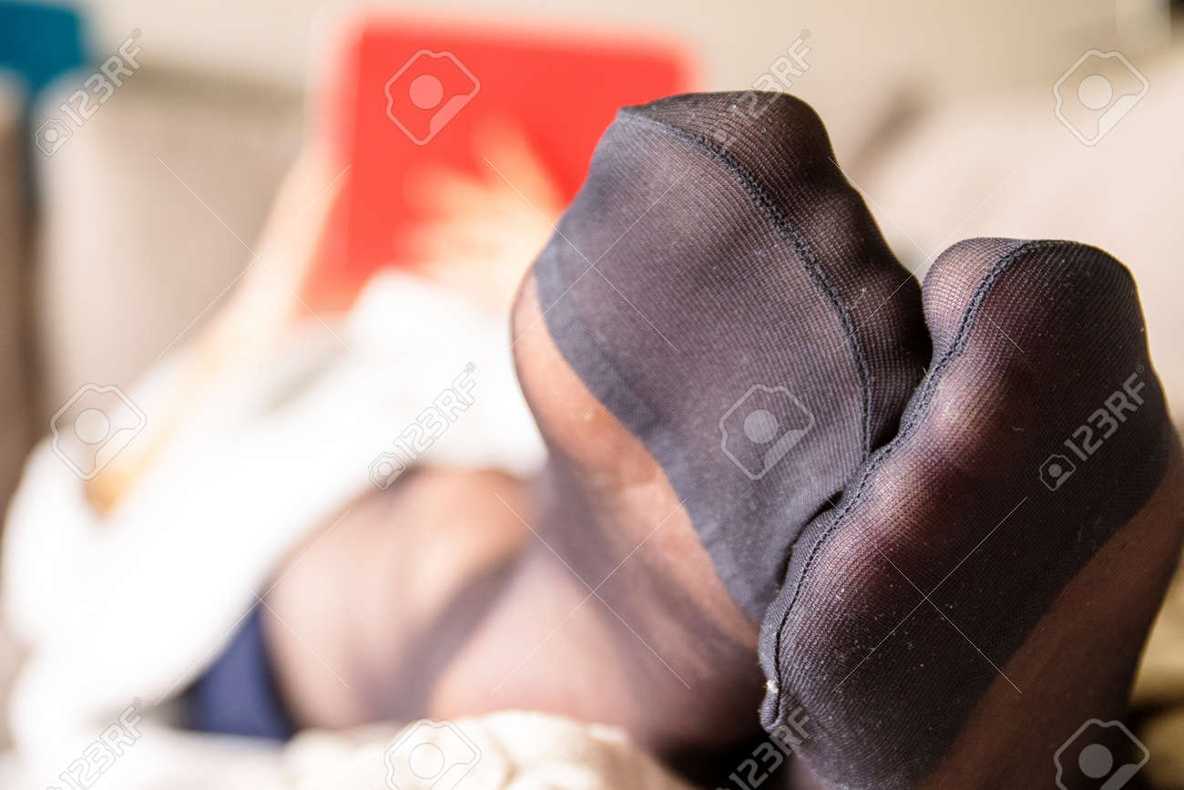 A close up of the black nylon feet of a woman dressed in pantyhose or stockings with reinforced toes, lying on a couch in a living room relaxing and using her tablet computer in the background. - 167681231