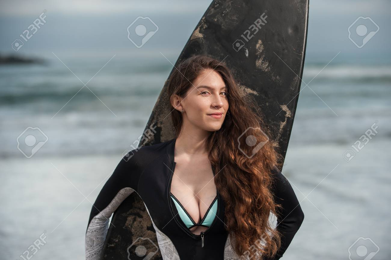 Sexy California surfer girl standing with back to board and waves