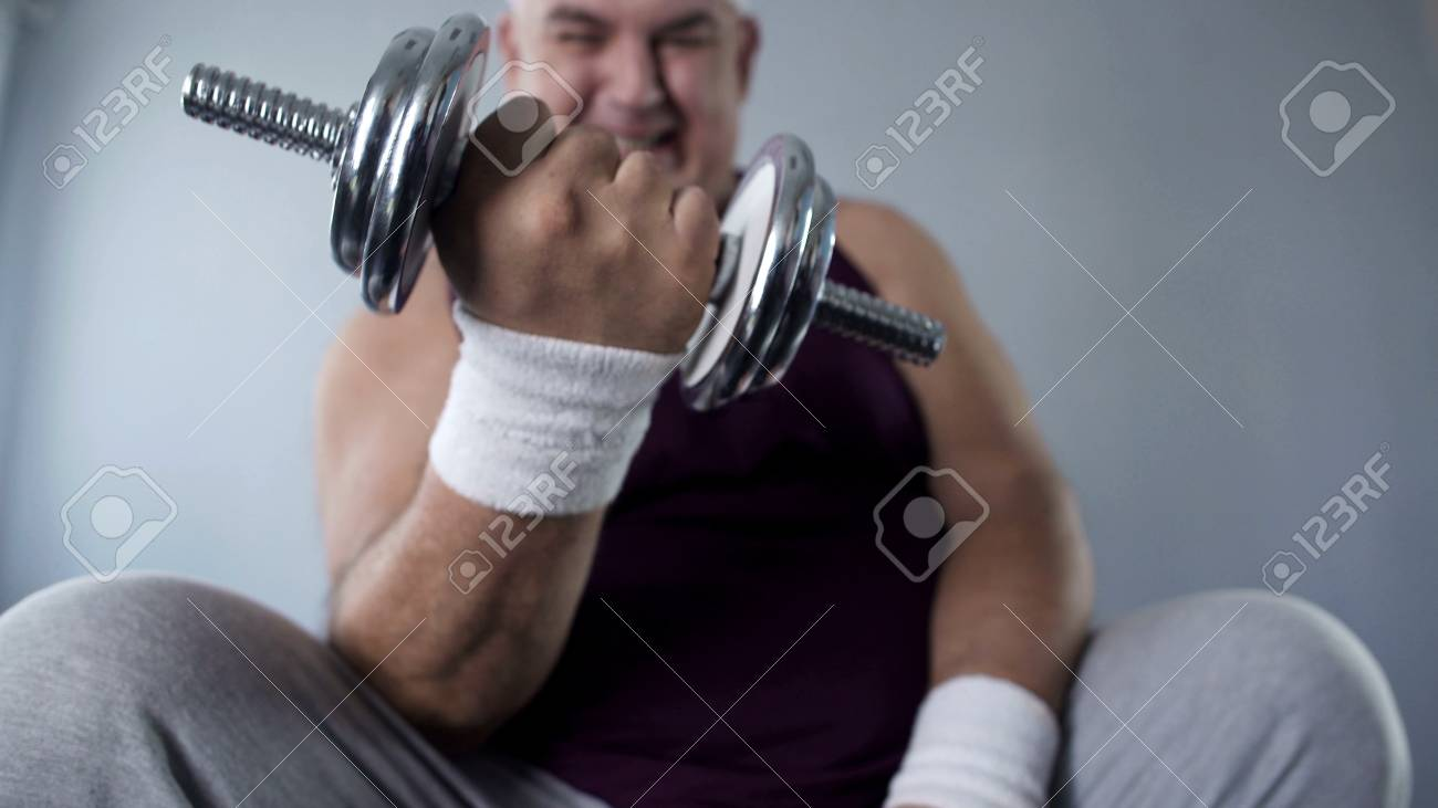 Purposeful obese man lifting dumbbells at home working hard