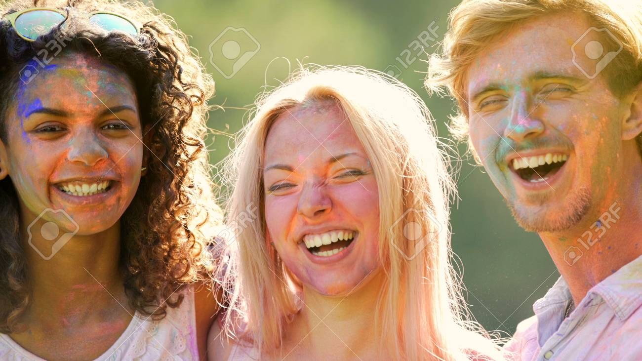 cheerful smiling faces of young people having fun at holi
