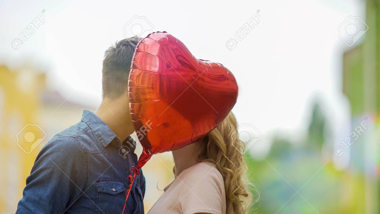 Happy Couple Kissing, Hiding Behind Heart Balloon, Romantic