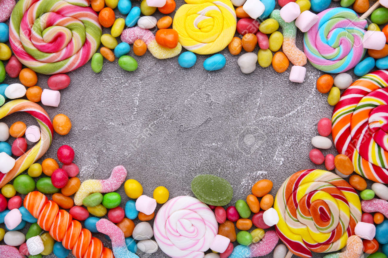 Colorful lollipops and different colored round candy on concrete - 154900478