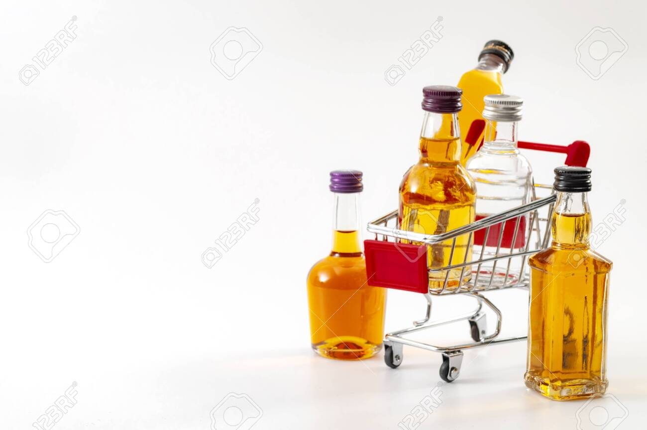 Buy booze, shopping the liqueur aisle and purchase of alcoholic beverages concept theme with mini bottles of alcohol in a small supermarket cart isolated on white background with copy space - 152400751