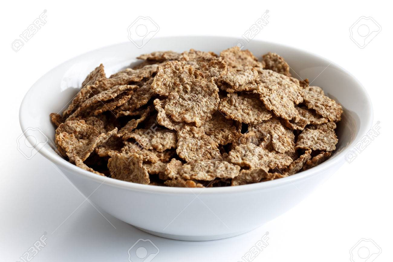 Wheat bran breakfast cereal with no milk in a bowl isolated on