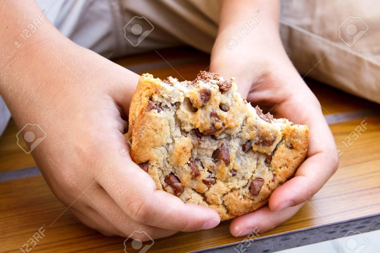 Lenfant Détient Un Petit Biscuit Fait Maison Au Chocolat à Moitié