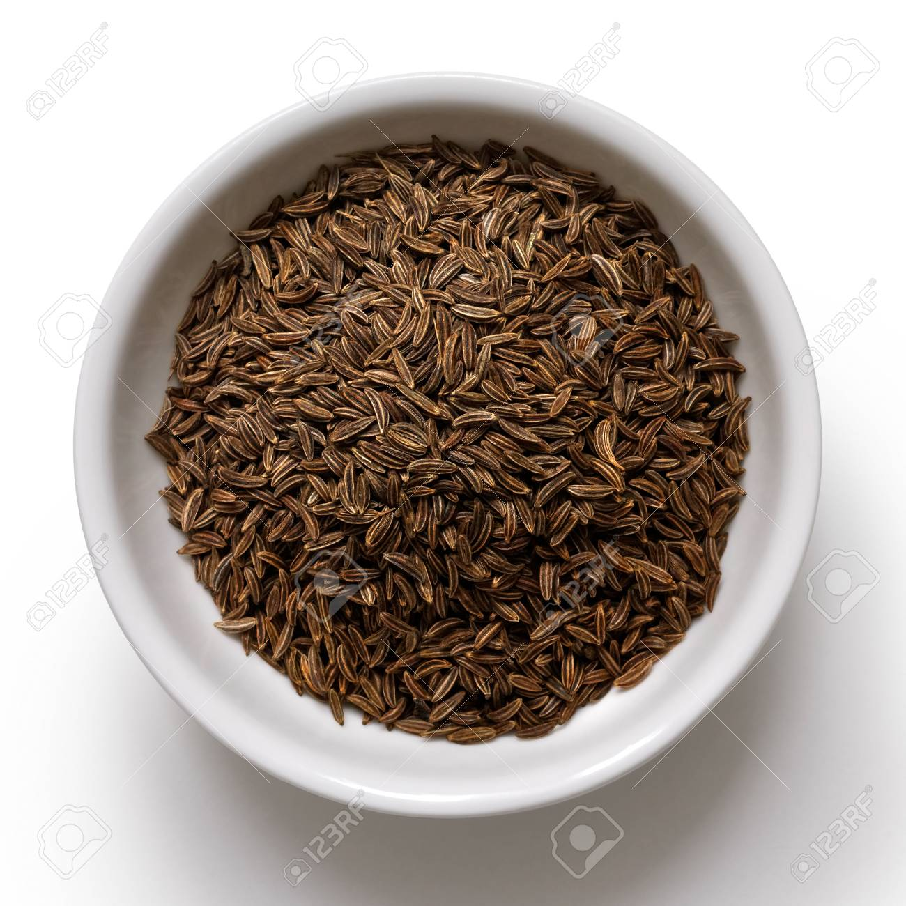 Caraway or cumin seeds in white ceramic bowl isolated on white