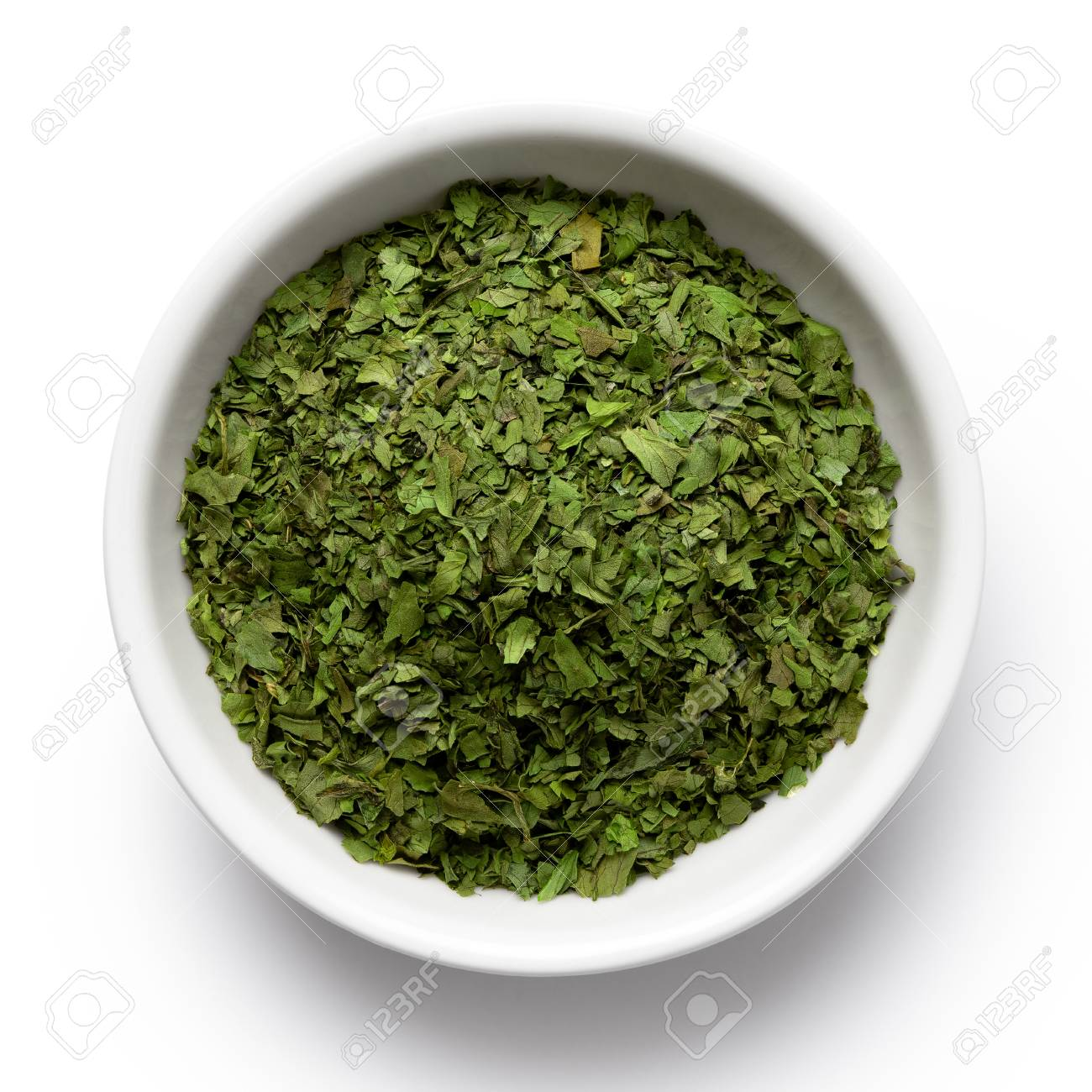 Dried chopped coriander leaves in white ceramic bowl isolated on white from above. - 117174692