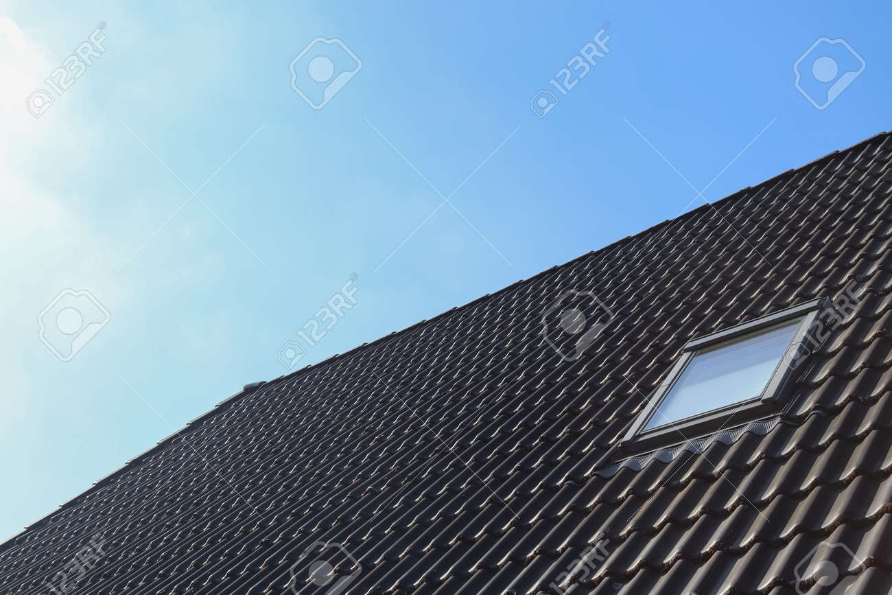 Roof window in velux style with black roof tiles - 169911347