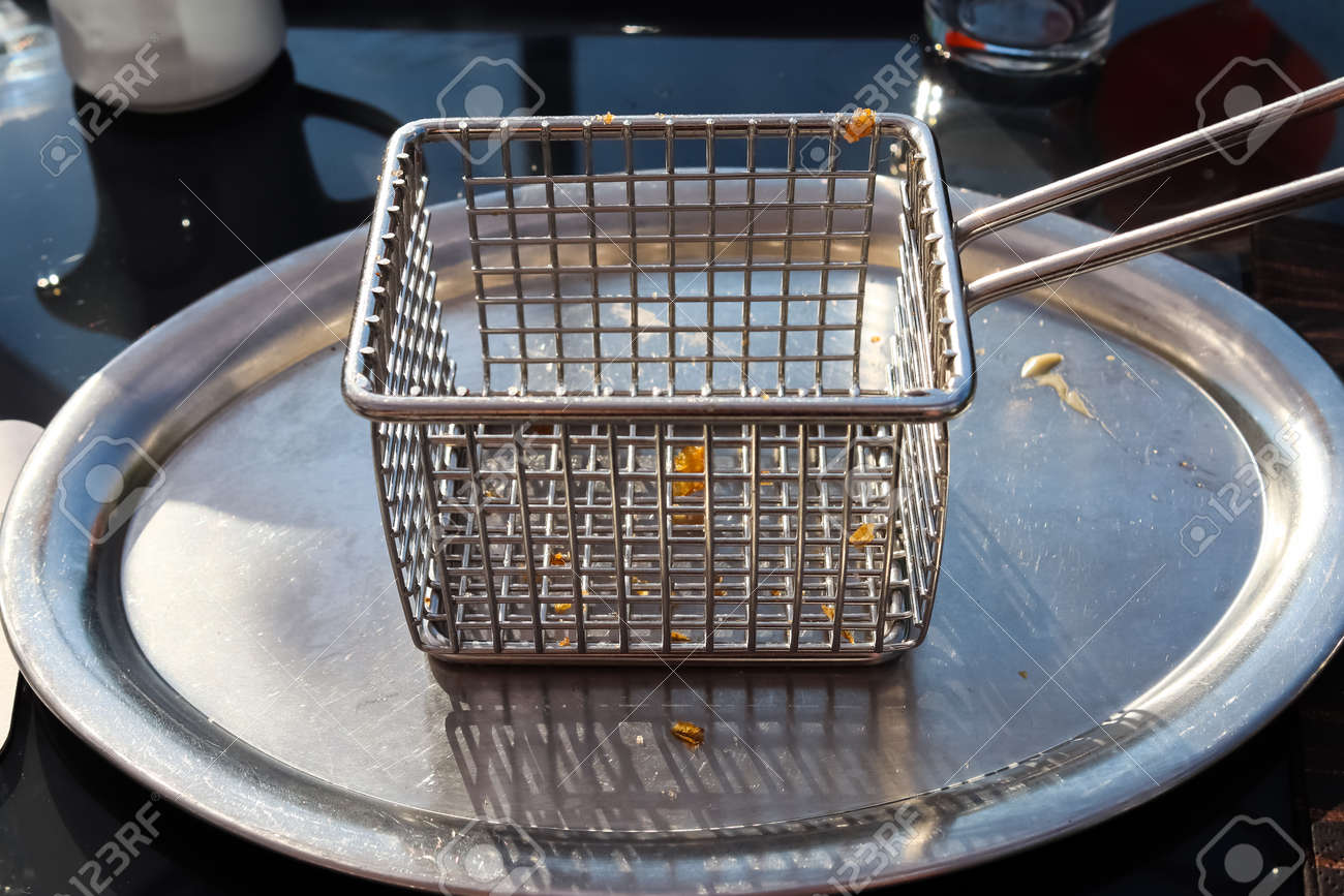 Empty metallic deep fryer on a table with some little fries pieces - 169911819