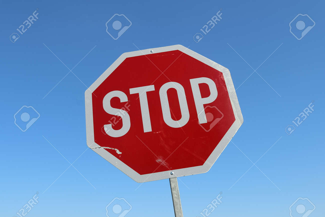 Close up of a stop sign against a clear blue sky - 169911836