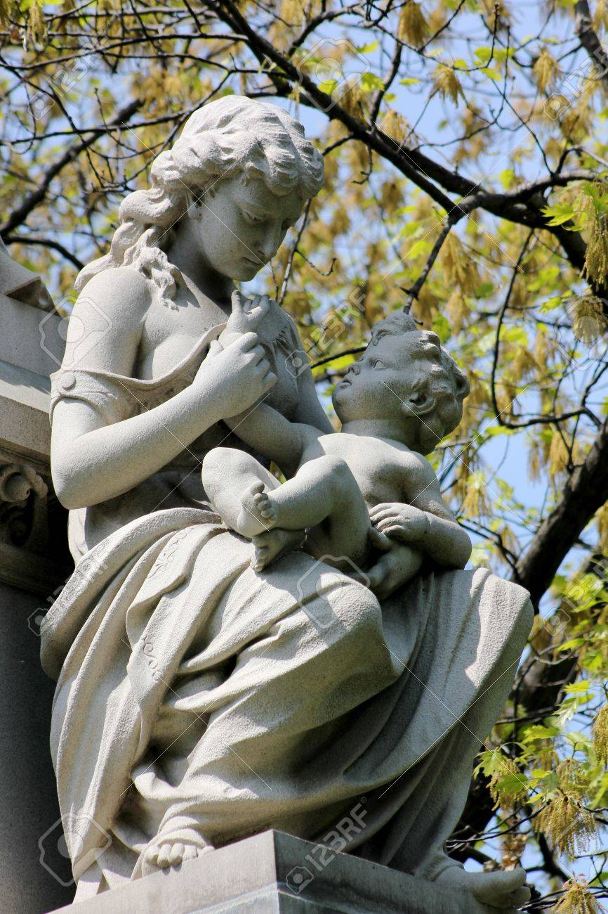 A stone statue of a young woman with a bare shoulder cradling a baby on her lap and holding his hand as he reaches for her face, on a tomb at Graceland Cemetery, Chicago, Illinois, USA Stock Photo - 20754728