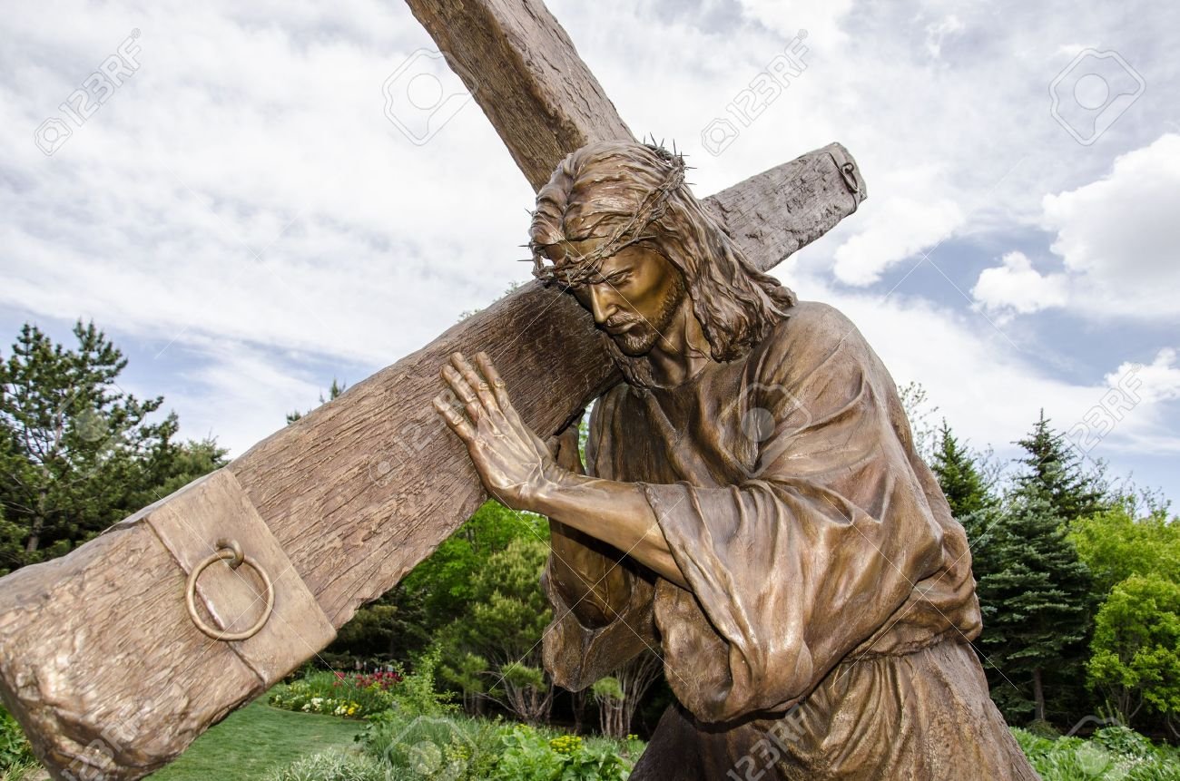 a detailed life size statue of jesus carrying the cross in the