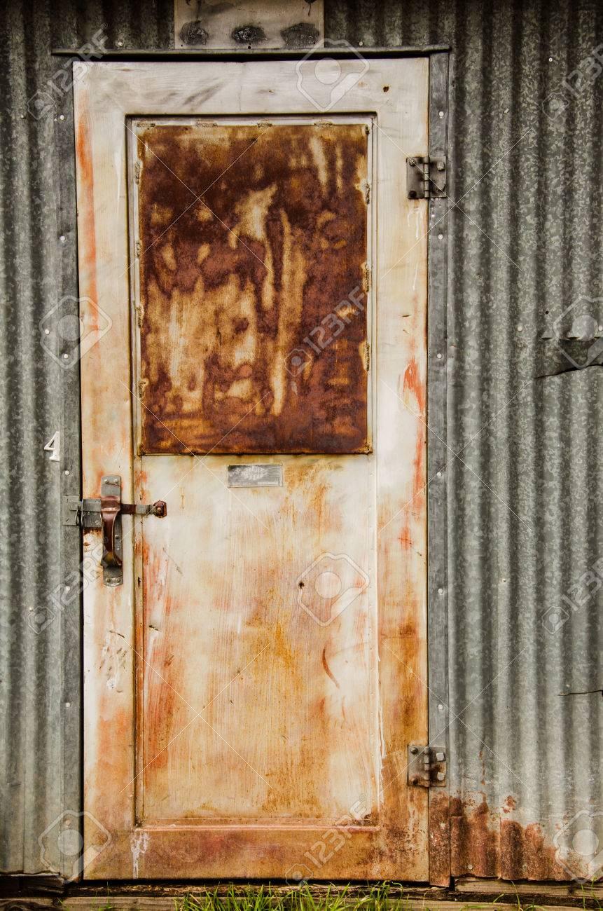 Rusty Metal Door rusty metal door and metal exterior wall on local farm stock photo