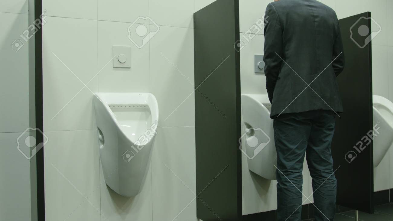 Man peeing to toilet bowl in restroom. Long shot Stock Photo - 91131245
