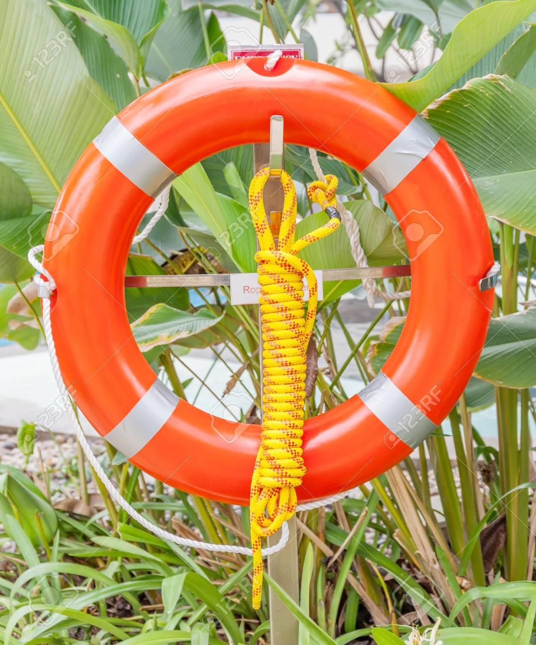 la bouée de sauvetage orange est suspendue autour de la piscine et le fond  d'arbre vert, concept de sécurité et de sauvetage.