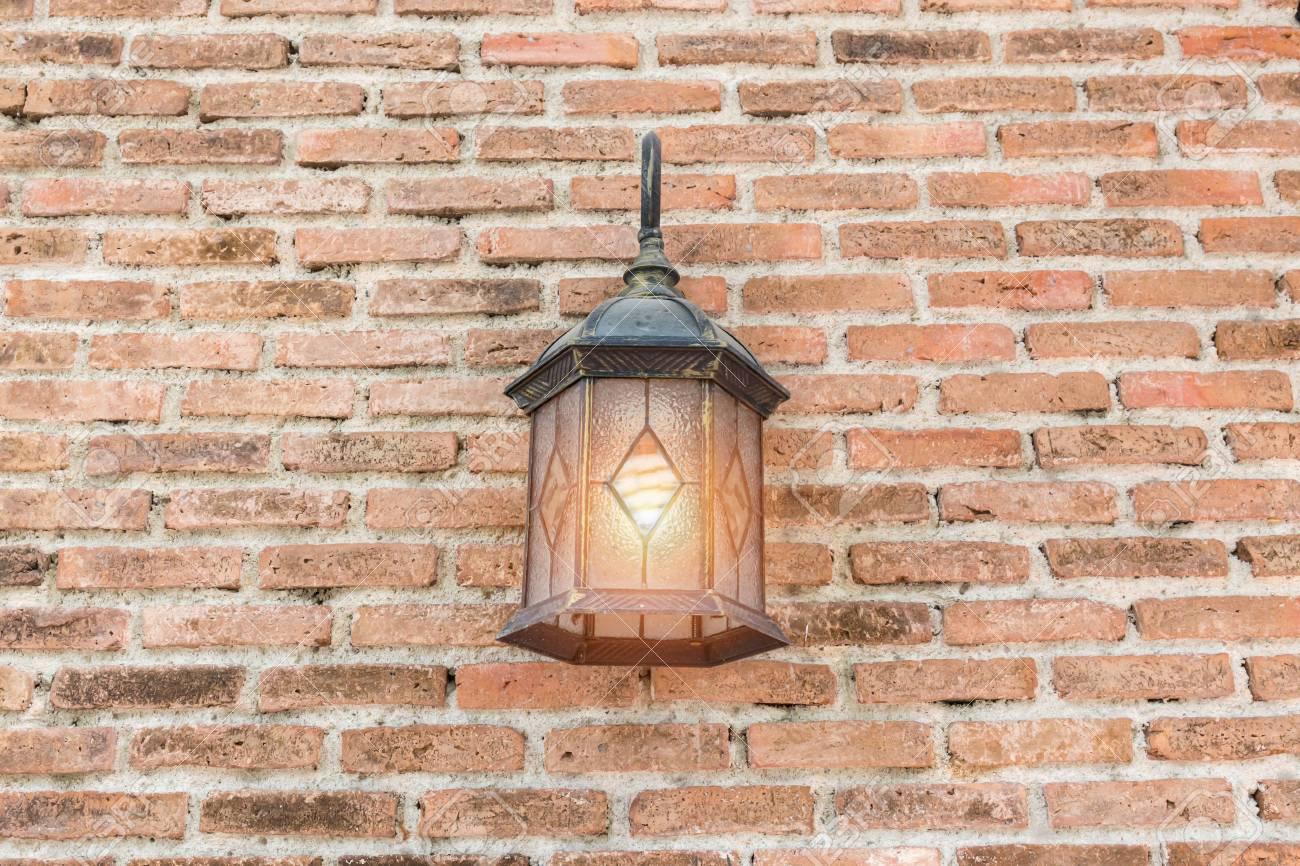 exterior vintage wall lamp illuminated on brick wall building stock
