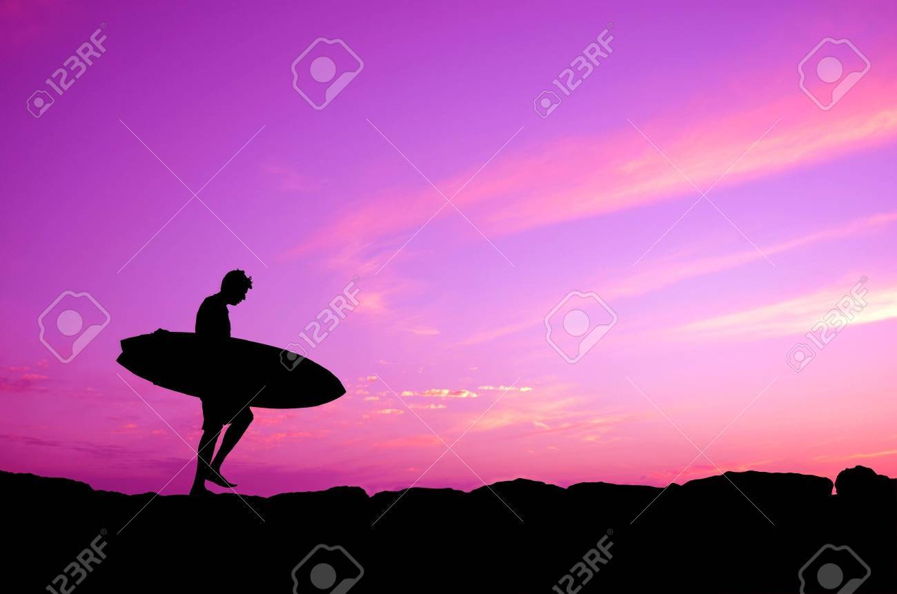 Vacation Silhouette Of A Surfer Carrying His Board Against A Purple Sunset Stock Photo - 20558210