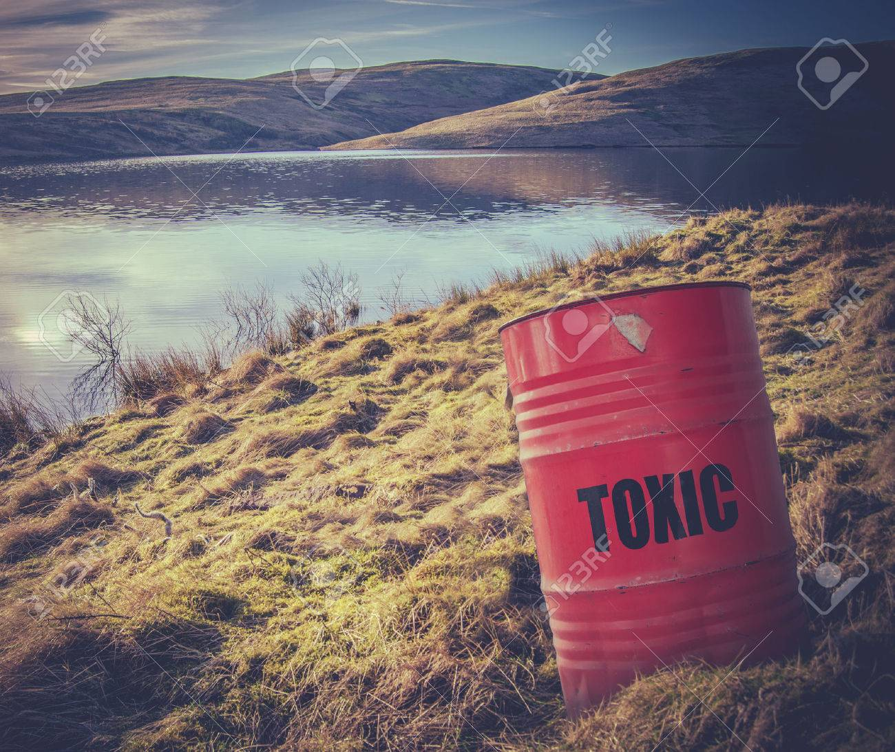 Conceptual Image Of A Toxic Waste Barrel Or Drum Near Water In The Countryside - 32228915