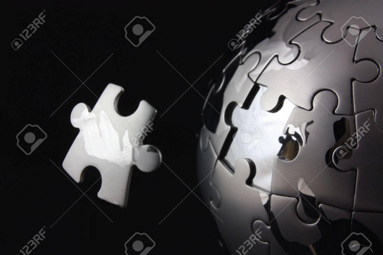 Floating jigsaw peice over chrome puzzle globe Stock Photo - 6097171