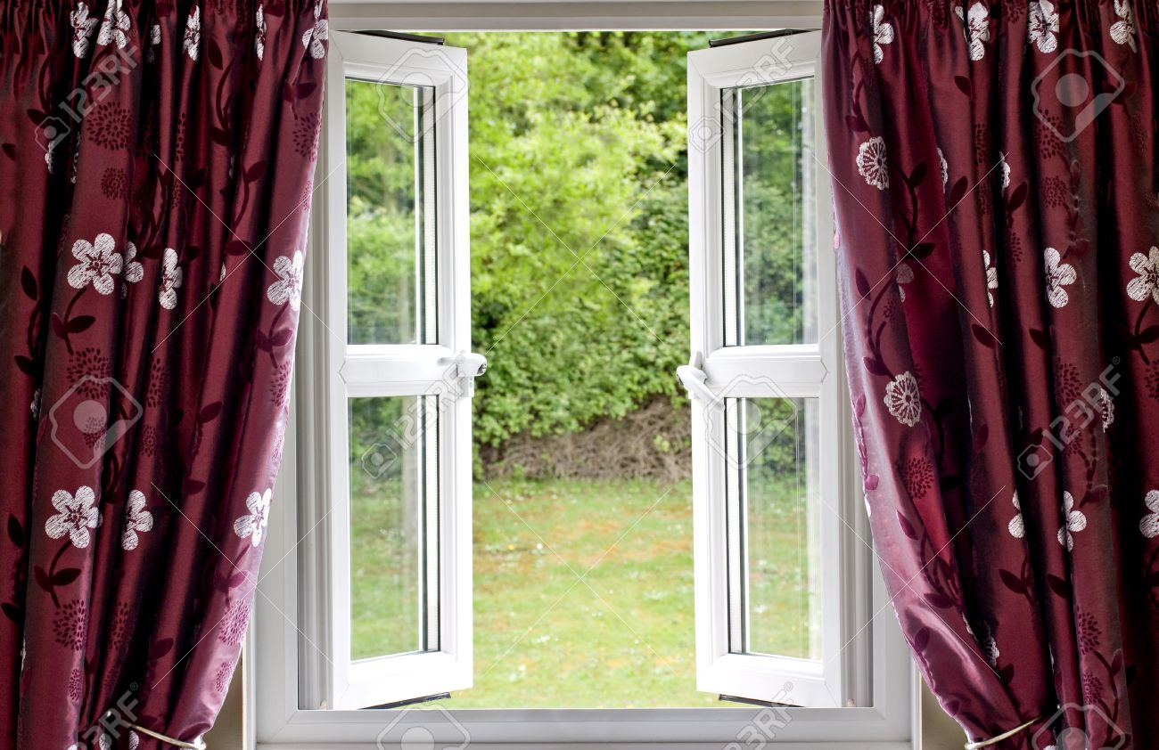 Open Window Draped In Curtains With A View Stock Photo