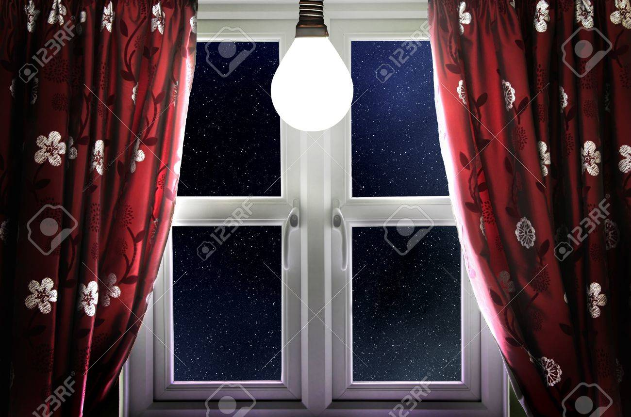 Light Bulb Shining In Window With Curtains Stock Photo   16562842
