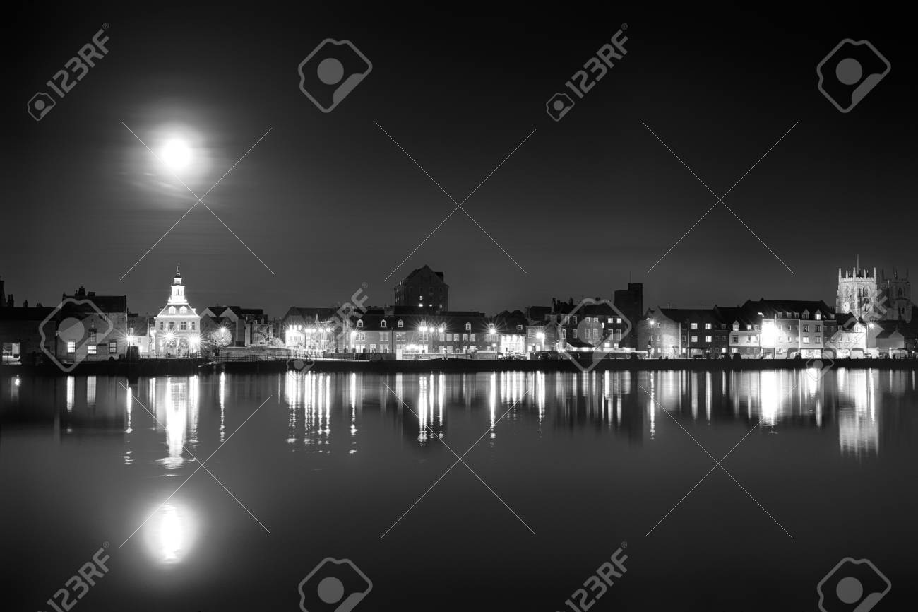 Stock photo supermoon rising over kings lynn harbour in norfolk uk black and white landscape of building night lights and water reflection light up the