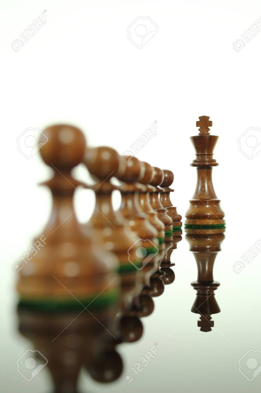 Chess king standing out from his pawns. - 10544692