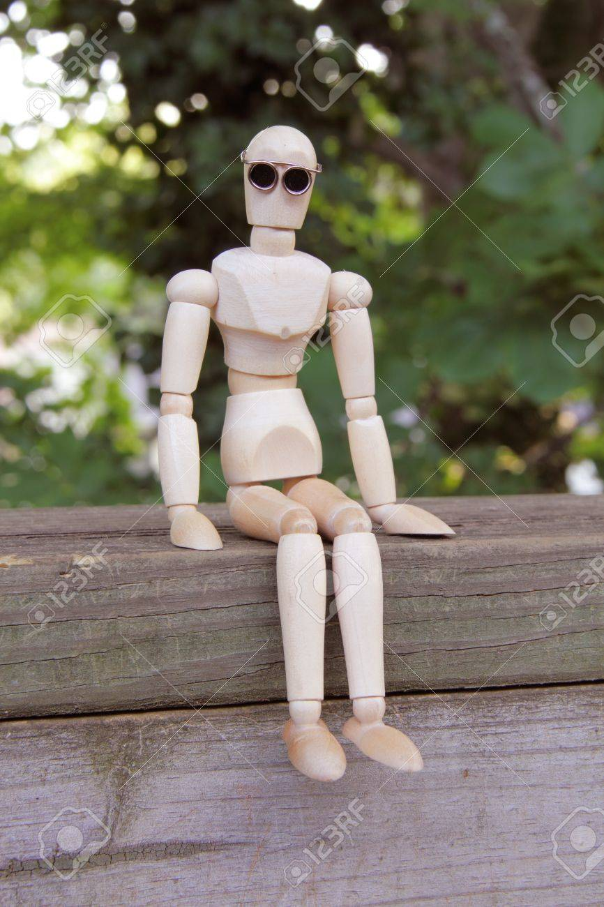 Wooden artist manikin sitting on a wooden fence and looking at the camera Stock Photo - 14363531