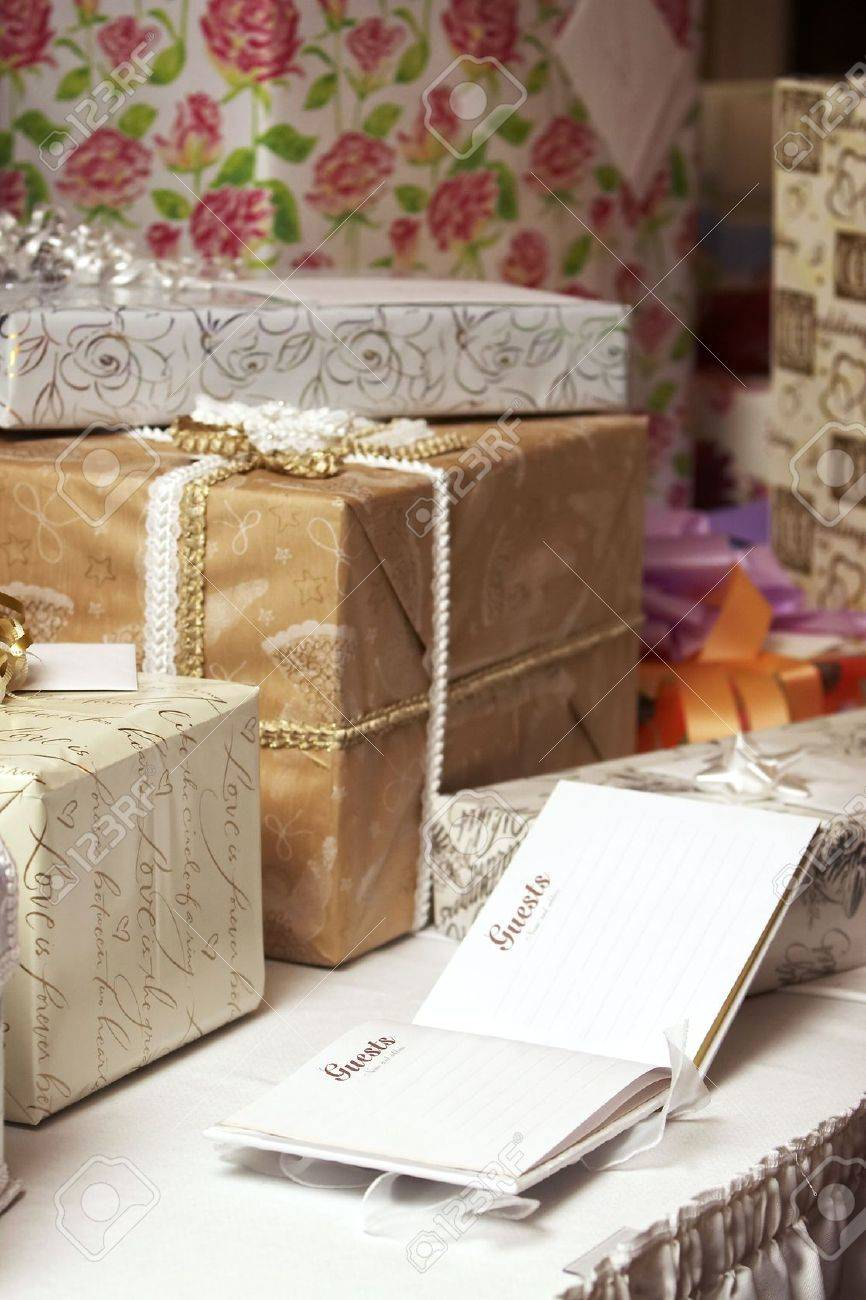 A blank guest book at a wedding or birthday with presents on a table, wrapping says: Like the circle of a ring love is forever Stock Photo - 607727